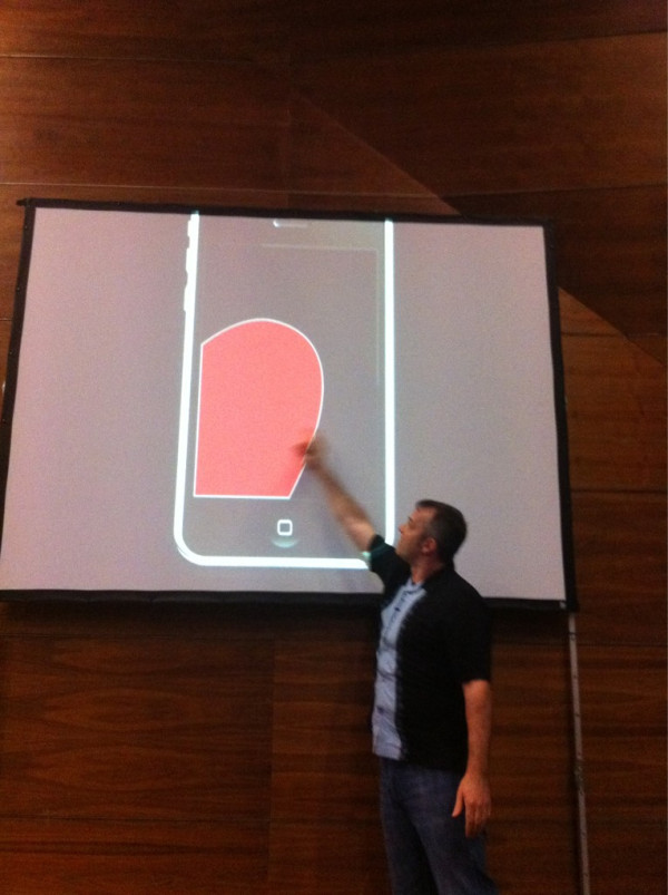 Josh Clark demonstrating optimal thumb range on an iPhone
